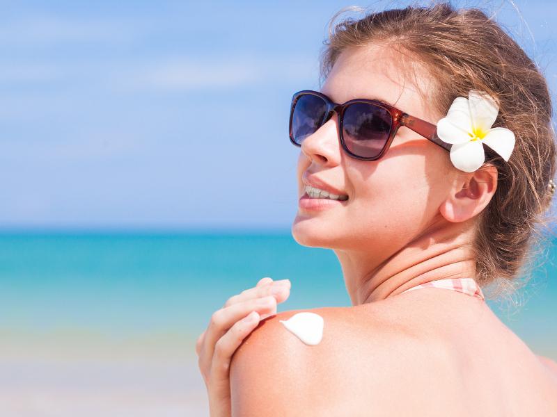 young-woman-in-sunglasses-putting-sun-cream-on-shoulder_1.bin