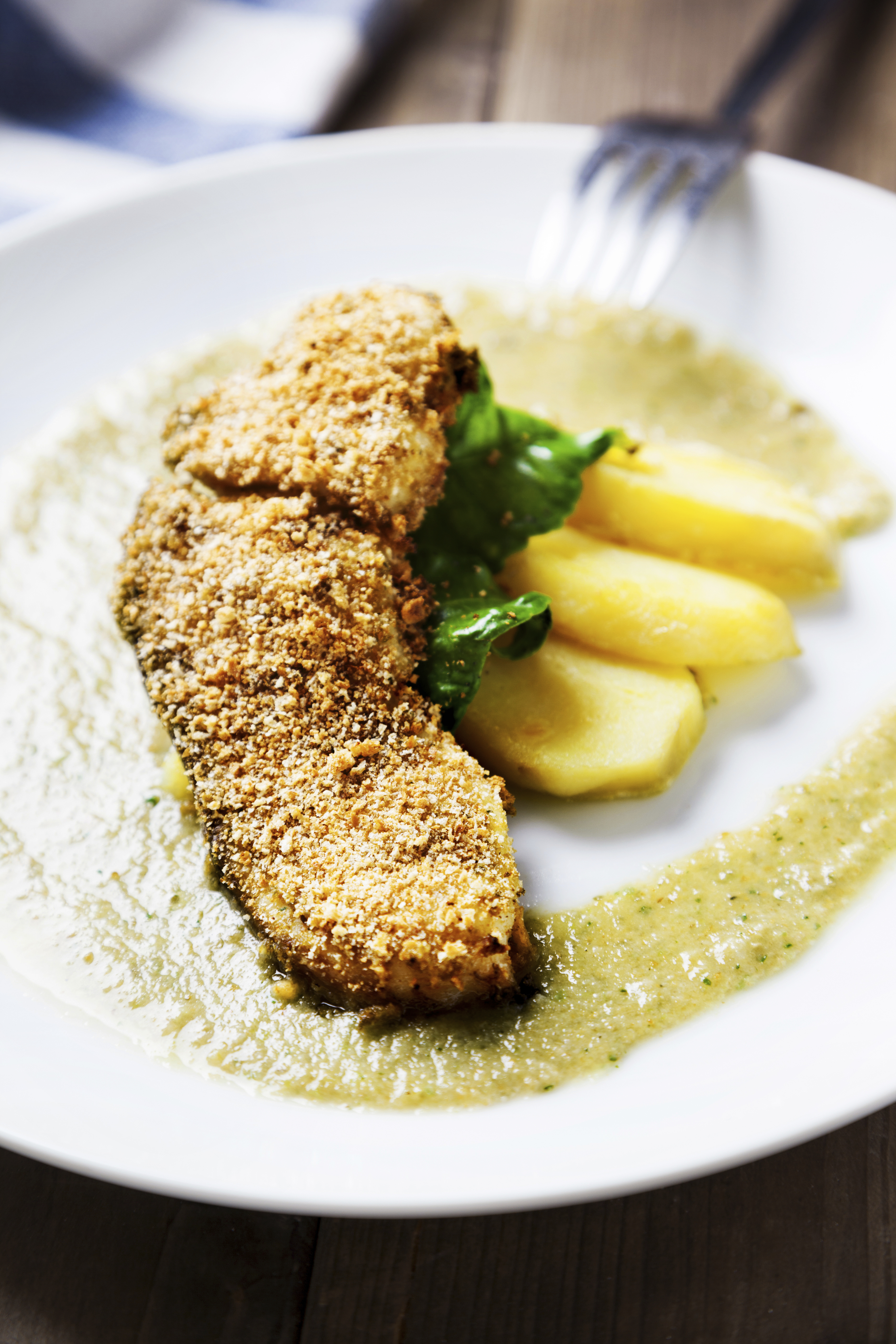 breaded swordfish in the plate served with potatoes and green sauce