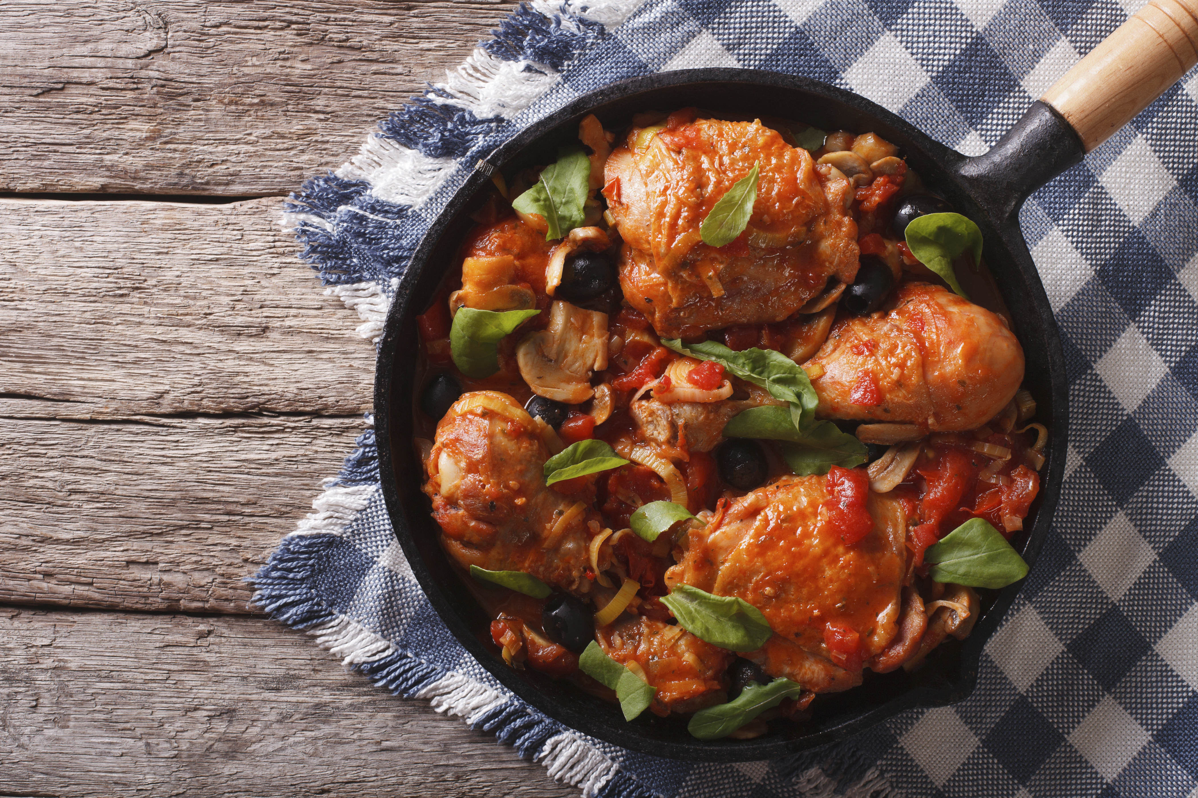 Cacciatori Chicken with mushrooms and black olives in a frying pan. horizontal top view