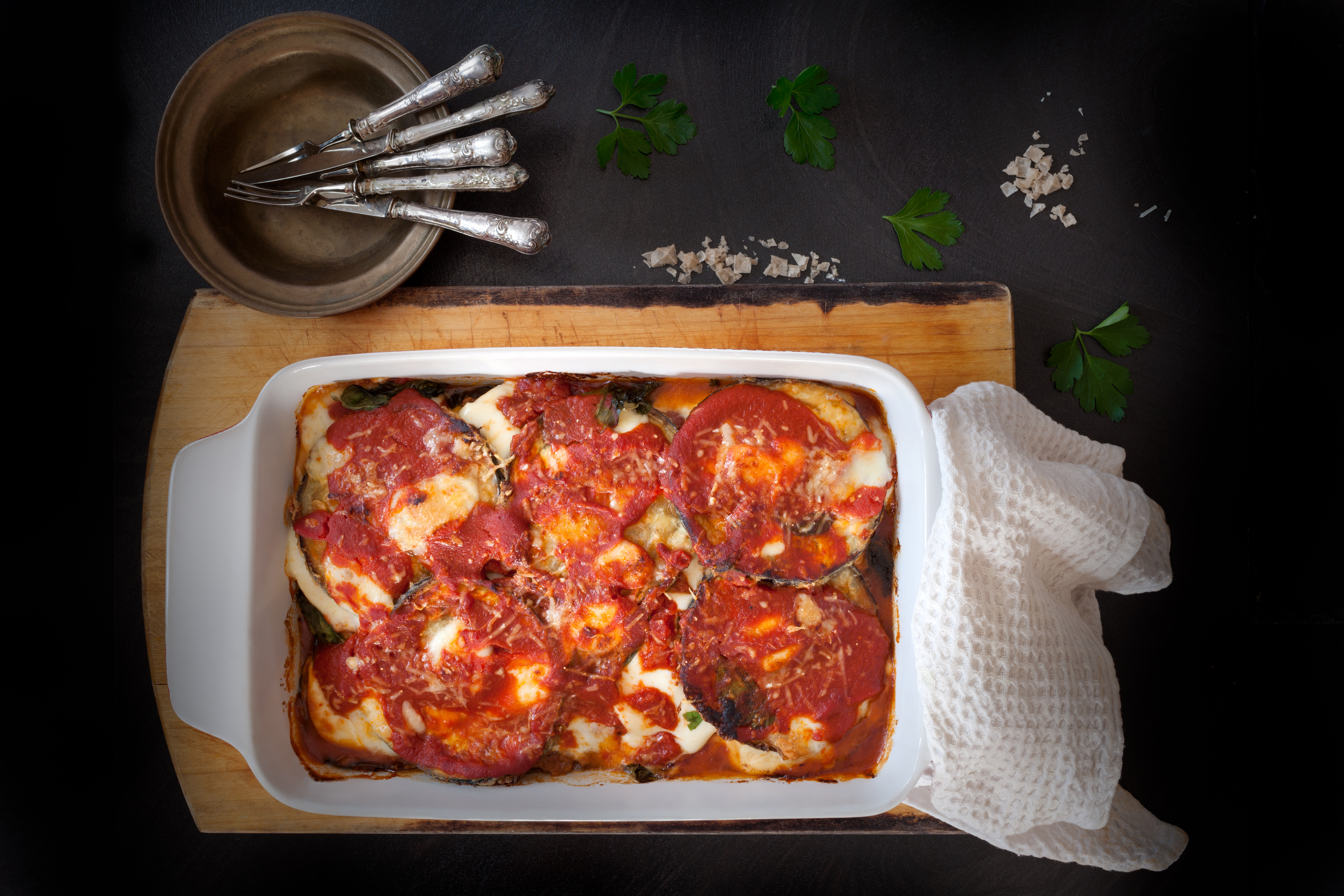 Top view of baking pan with eggplant parmigiana, typical recipe of the Italian cuisine.