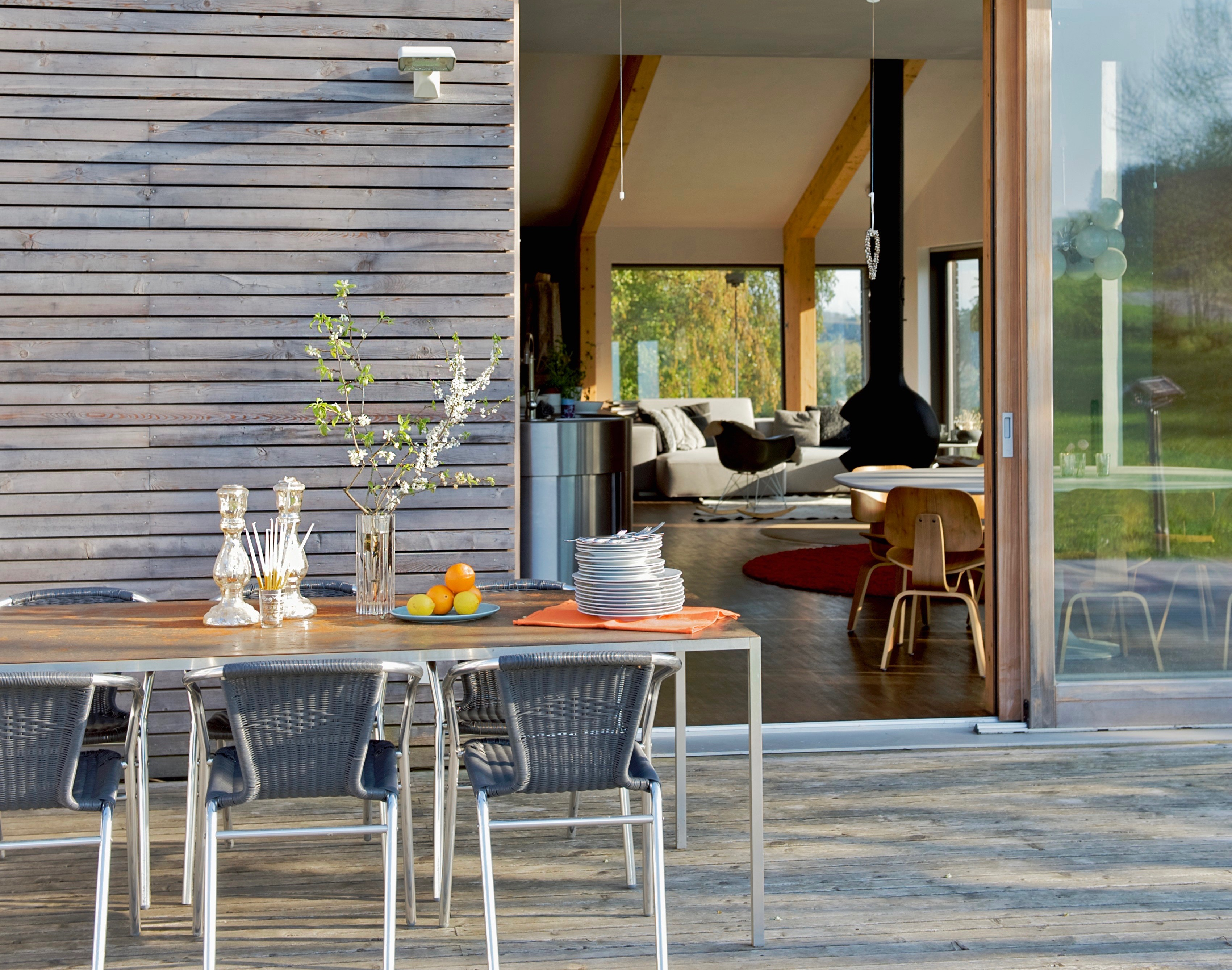 Table and chairs on terrace of contemporary house with exterior wood cladding and view of living room through open terrace door