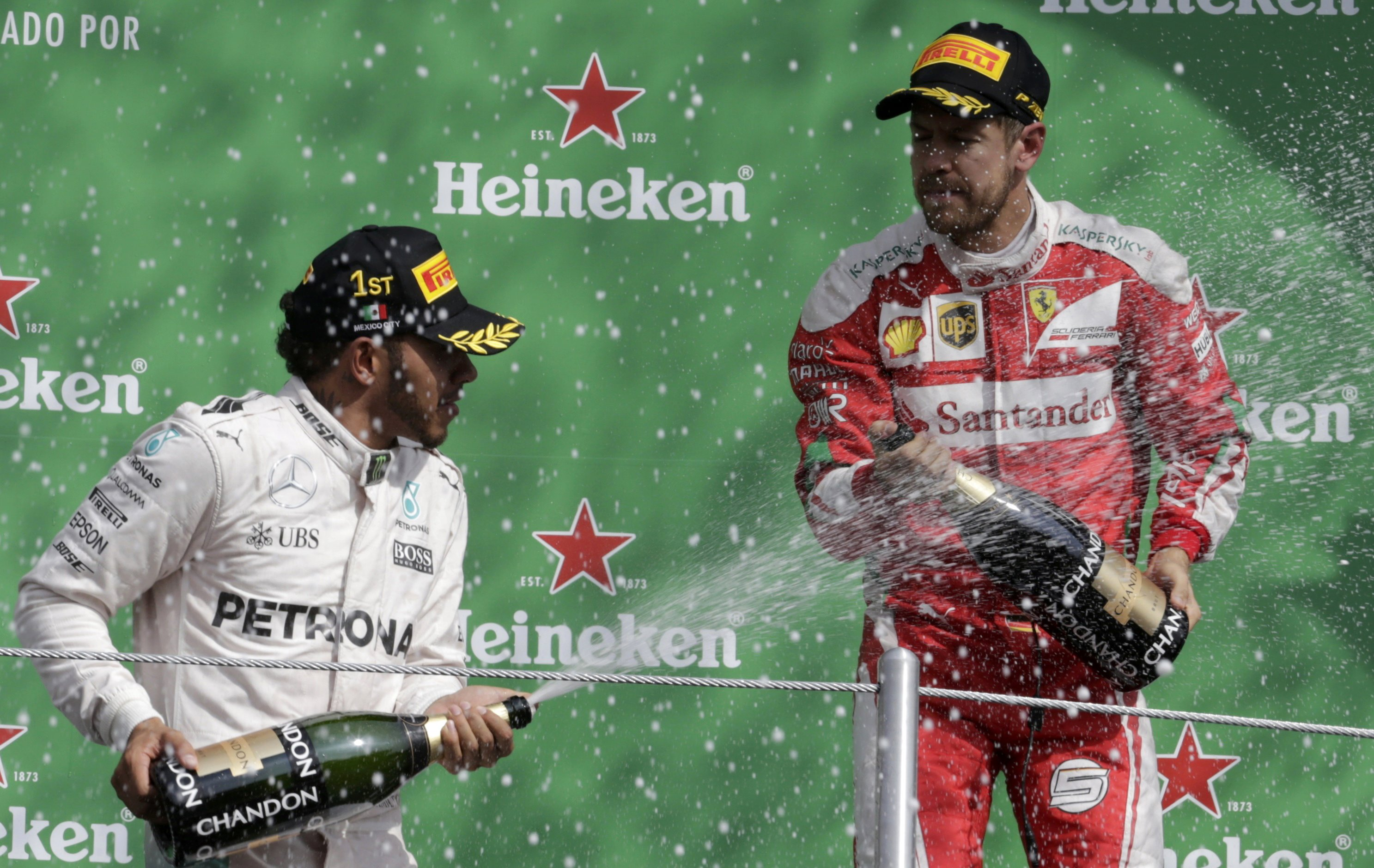 Formula One - F1 - Mexican F1 Grand Prix - Mexico City, Mexico - 30/10/16 - Race winning Mercedes' driver Lewis Hamilton of Britain (L) sprays champagne with third placed finishing Ferrari driver Sebastian Vettel of Germany. REUTERS/Henry Romero