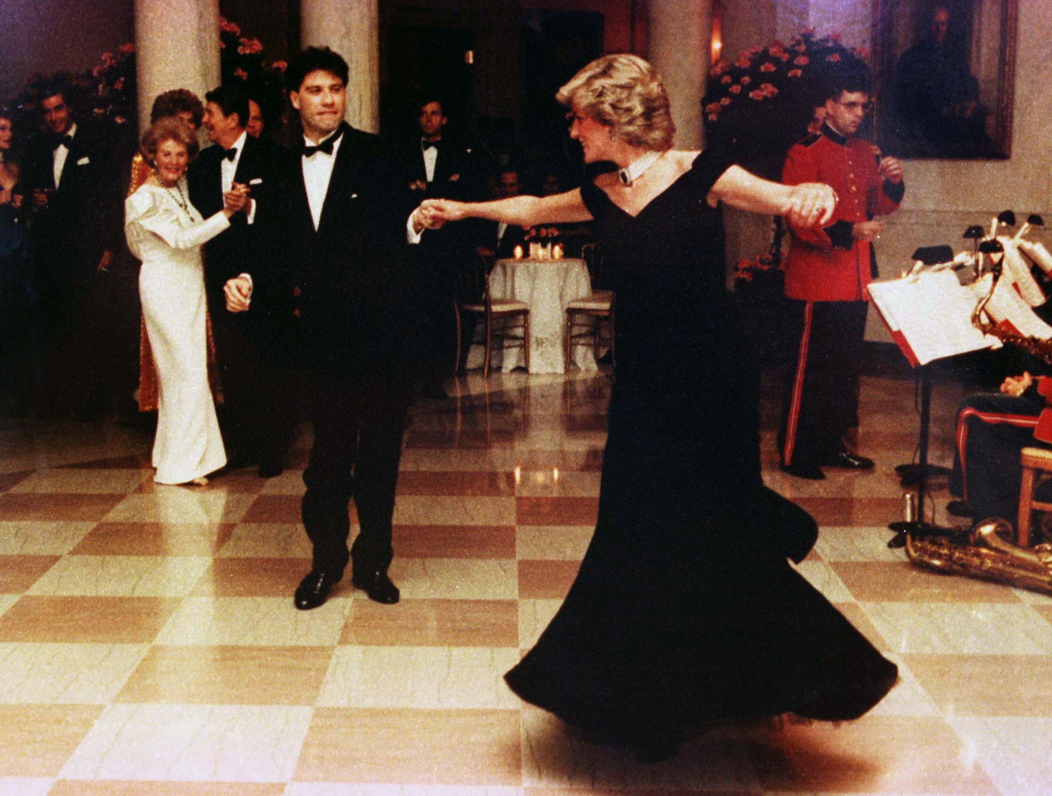 NOVEMBER 1985 FILE PHOTO- Princess Diana is shown wearing a Victor Edelstein gown as she dances at a November 9, 1985 White House dinner with actor John Travolta. The ink-blue Edelstein gown sold for 2,500 during an auction at Christie's auction house in New York June 25, the highest price paid for any one of the 79 gowns worn by the Princess and auctioned to raise funds for AIDS and cancer charities in Britain and the United States.  DIANA - RTR4SM0