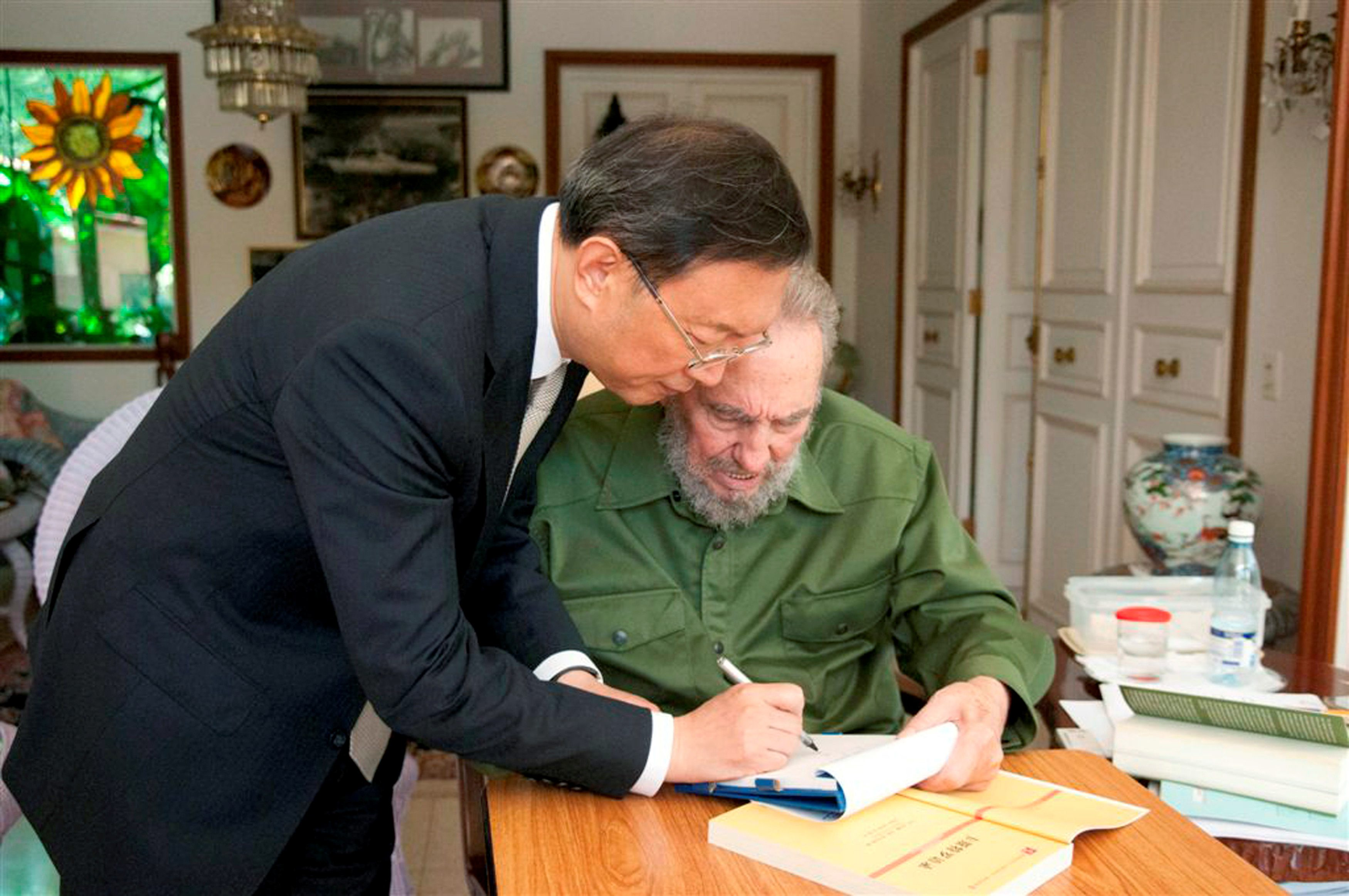 China's Foreign Minister Yang Jiechi (L) writes in a notebook as former Cuban leader Fidel Castro holds it during a meeting in Havana in this August 1, 2010 file photo.  REUTERS/Roberto Chile/File Photo    EDITORIAL USE ONLY.