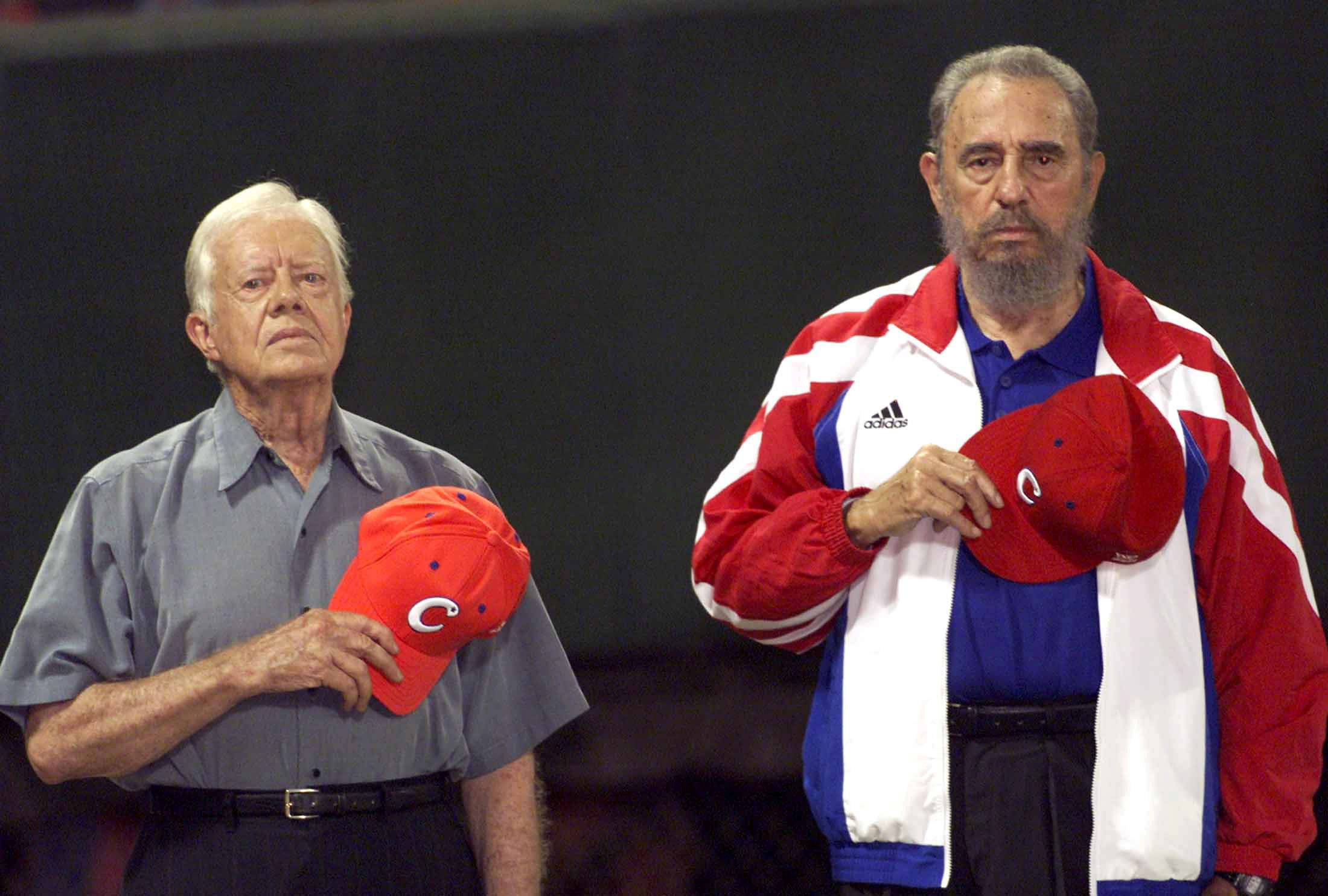 Former U.S. President Jimmy Carter and then Cuban President Fidel Castro (R) listen to the Cuban national anthem at the baseball stadium