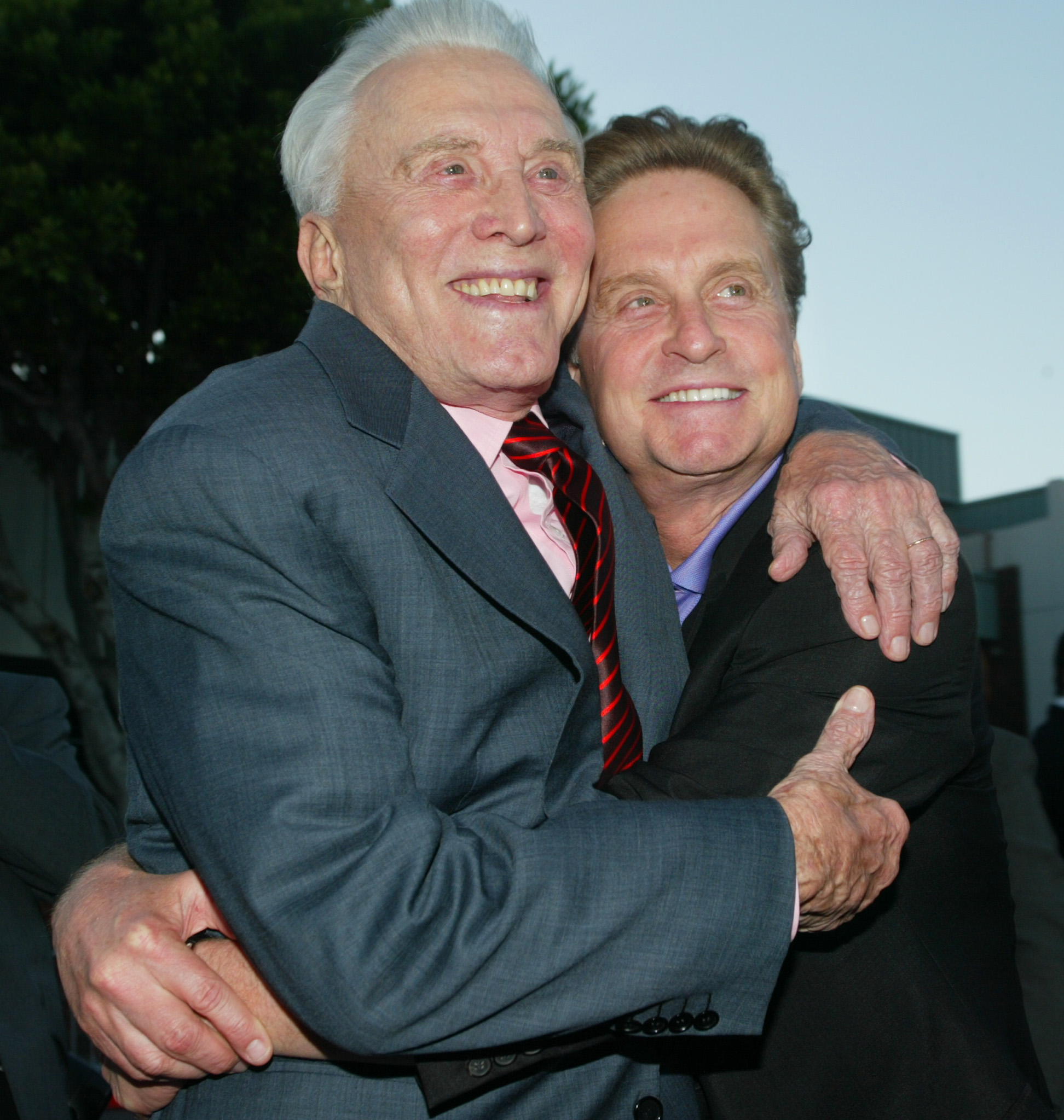 Actor Kirk Douglas (L) hugs his son, actor Michael Douglas as they arrive for the premiere of their new film