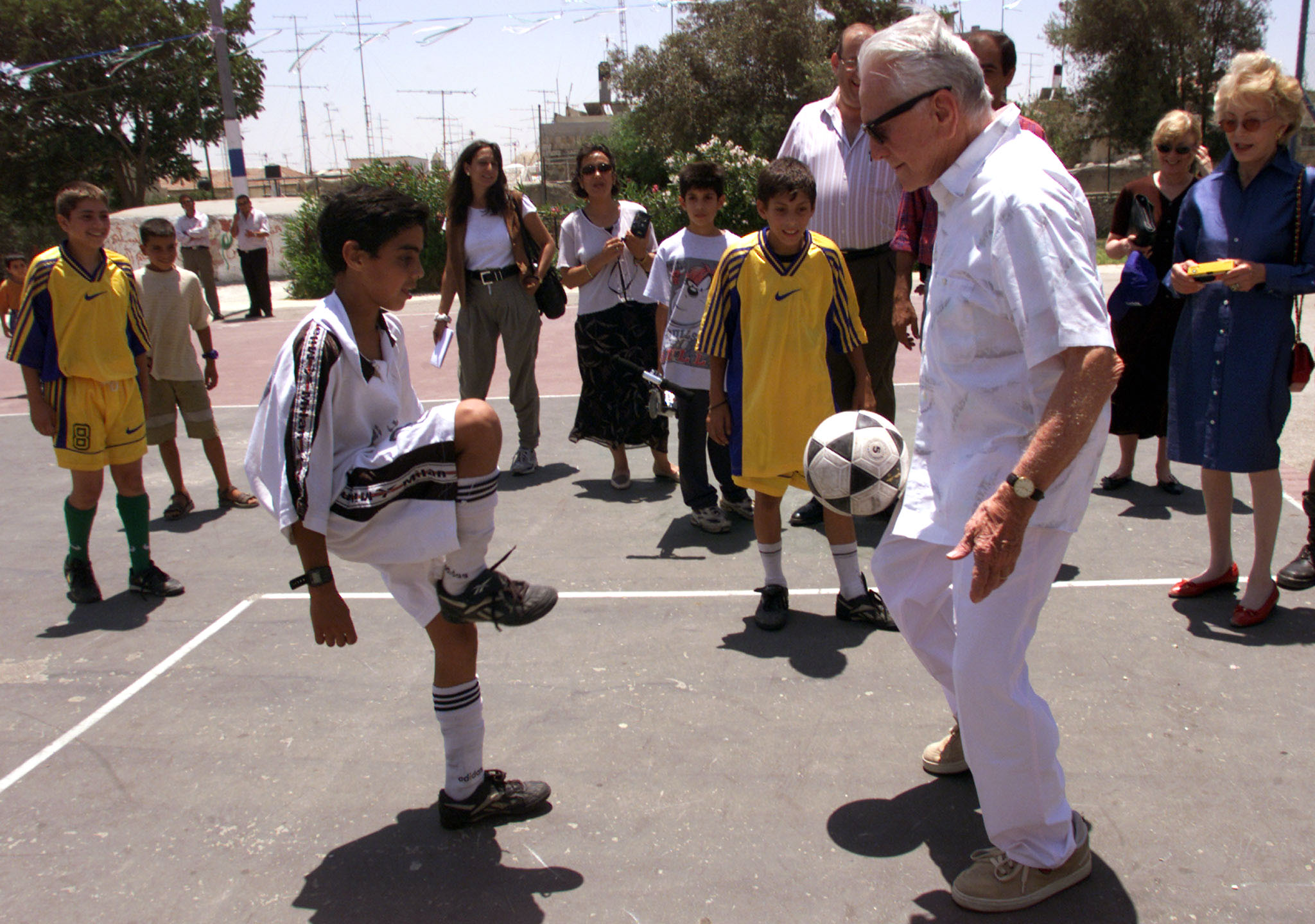 U.S. actor Kirk Douglas plays football with Palestinian children in a playgound he and his wife have donated to the Muslim Quarter of Jerusalem's Old City, July 17. Douglas and his wife Ann have donated five playgrounds to Israeli children and say the one in the Muslim Quarter is special because it represents their hope for a future peace for all Israeli children. - RTXJVQ1