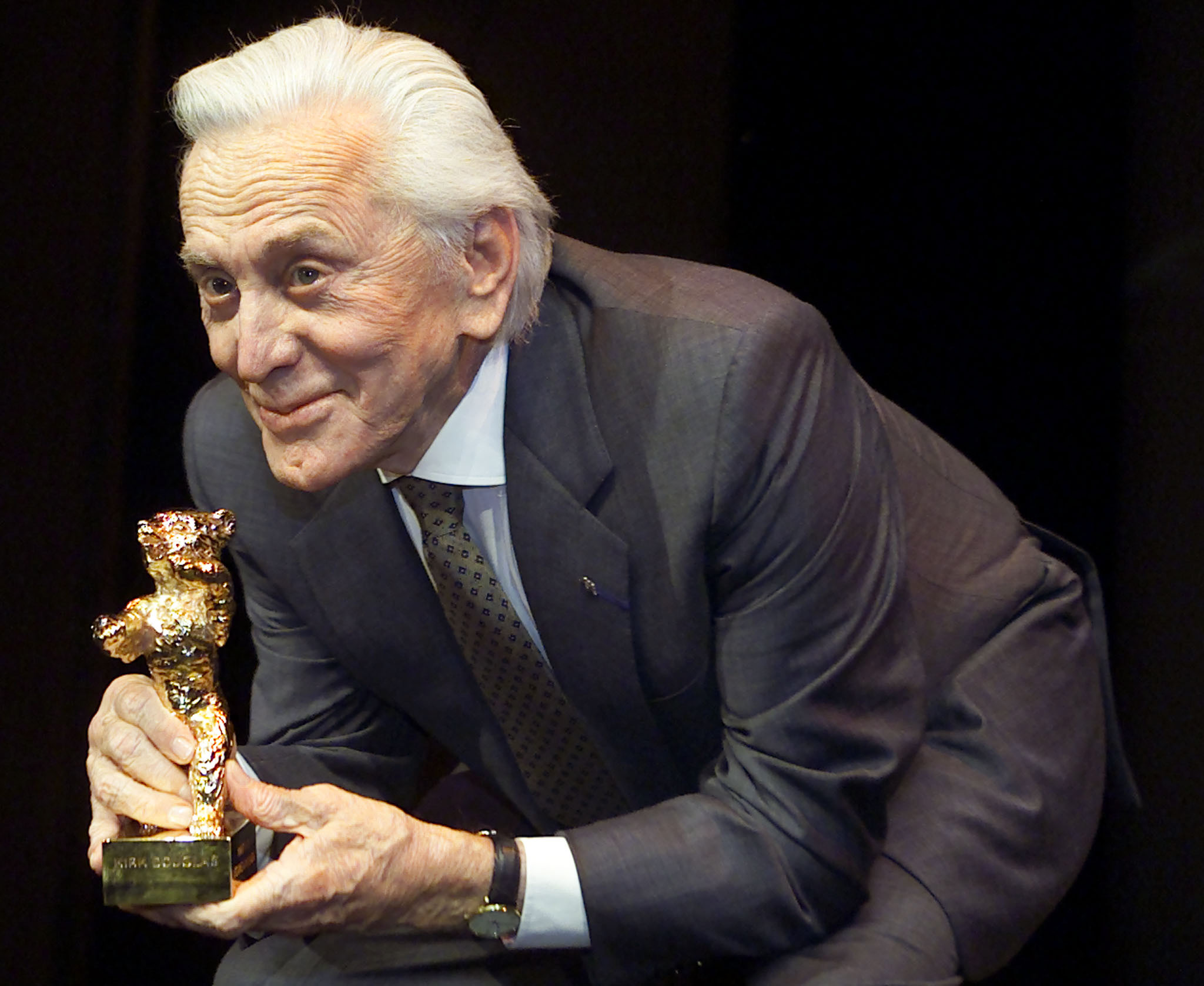 U.S. actor Kirk Douglas bends down as he poses with his Golden Bear for the media during an awards ceremony at the 51st Berlinale International Film Festival in Berlin February 16, 2001.  Douglas received the Golden Bear award for his lifetime achievements. - RTXKB94
