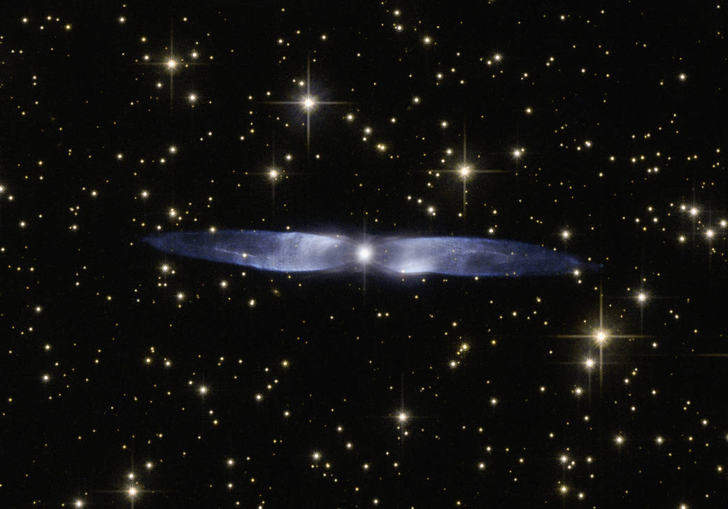 In this cosmic snapshot, the spectacularly symmetrical wings of Hen 2-437 show up in a magnificent icy blue hue. Hen 2-437 is a planetary nebula, one of around 3000 such objects known to reside within the Milky Way. Located within the faint northern constellation of Vulpecula (The Fox), Hen 2-437 was first identified in 1946 by Rudolph Minkowski, who later also discovered the famous and equally beautiful M2-9 (otherwise known as the Twin Jet Nebula). Hen 2-437 was added to a catalogue of planetary nebula over two decades later by astronomer and NASA astronaut Karl Gordon Henize. Planetary nebulae such as Hen 2-437 form when an aging low-mass star â such as the Sun â reaches the final stages of life. The star swells to become a red giant, before casting off its gaseous outer layers into space. The star itself then slowly shrinks to form a white dwarf, while the expelled gas is slowly compressed and pushed outwards by stellar winds. As shown by its remarkably beautiful appearance, Hen 2-437 is a bipolar nebula â the material ejected by the dying star has streamed out into space to create the two icy blue lobes pictured here.