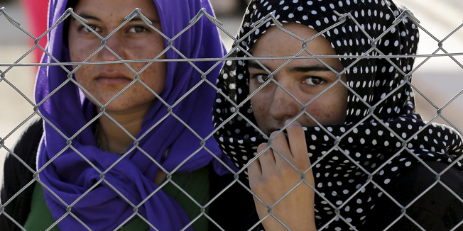 Yazidi refugees stand behind fences as they wait for the arrival of United Nations High Commissioner for Refugees Special Envoy Angelina Jolie at a Syrian and Iraqi refugee camp in the southern Turkish town of Midyat in Mardin province, Turkey, June 20, 2015. REUTERS/Umit Bektas      TPX IMAGES OF THE DAY      - RTX1HEPQ