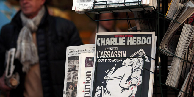 "A copy of the latest edition of French weekly newspaper Charlie Hebdo with the title ""One year on, The assassin still on the run"" is displayed at a kiosk in Nice, France, January 6, 2016. France this week commemorates the victims of last year's Islamist militant attacks on satirical weekly Charlie Hebdo and a Jewish supermarket with eulogies, memorial plaques and another cartoon lampooning religion.      REUTERS/Eric Gaillard"