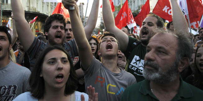 Members of Coalition of the Radical Left party (SYRIZA) shout slogans during Alexis Tsipras' speech in Athens, Thursday, May 3, 2012. The country will hold national elections this Sunday, with opinion polls indicating no party will win enough of a majority to form a government without seeking the backing of another party to form a coalition. (AP Photo/Petros Giannakouris)