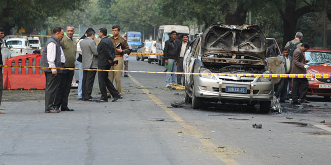 Investigators work the scene of a vehicle that exploded near the Israeli embassy in New Delhi on February 13, 2012.  An Israeli embassy car blew up February 13 in the Indian capital, injuring an Israeli diplomat and one other person, but it was not immediately known whether the explosion was caused by a bomb, officials said.   AFP PHOTO/SAJJAD HUSSAIN