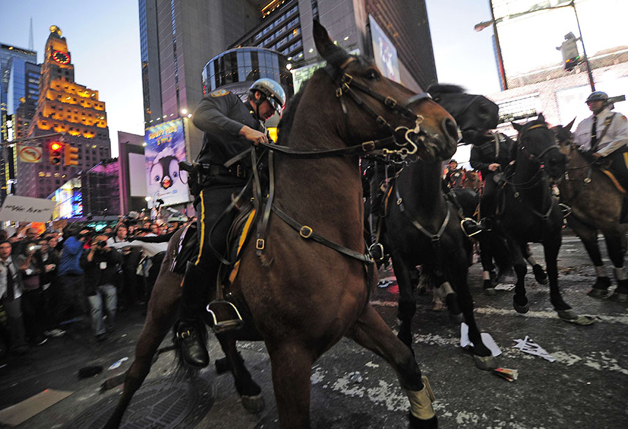 Mounted police stop Occupy Wall Street participants trying to break trough police barricade set stop them to take their demonstration onto the street on Times Square in New York, October 15, 2011. Thousands of demonstrators protesting corporate greed filled Times Square and some 15 demonstrators were handcuffed and loaded into a police van following confrontation with police. The Occupy Wall Street movement went global with groups spanning the globe from Asia to Europe, and in every U.S. state, staging demonstrations and other actions. AFP PHOTO/Emmanuel Dunand