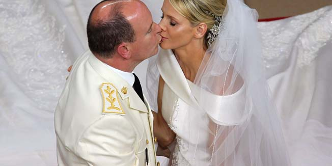 Prince Albert II of Monaco kisses Princess Charlene of Monaco during their religious wedding at the Main Courtyard of the Prince's Palace on July 2, 2011 in Monaco.  AFP PHOTO / VALERY HACHE