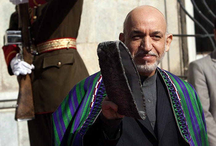 Afghan President Hamid Karzai waves as he waits to meet U.N. Secretary-General Ban Ki-moon in Kabul November 2, 2009. Ban made a surprise visit to Afghanistan on Monday as pressure grew to abandon plans for a risky run-off vote after the withdrawal of Karzai's only rival. REUTERS/Ahmad Masood(AFGHANISTAN POLITICS)