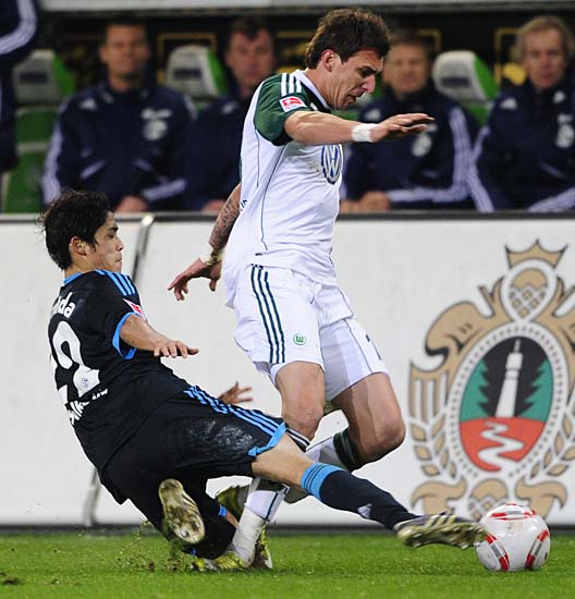 RESTRICTIONS / EMBARGO - ONLINE CLIENTS MAY USE UP TO SIX IMAGES DURING EACH MATCH WITHOUT THE AUTHORISATION OF THE DFL. NO MOBILE USE DURING THE MATCH AND FOR A FURTHER TWO HOURS AFTERWARDS IS PERMITTED WITHOUT THE AUTHORISATION OF THE DFL.Schalke's Japanese defender Atsuto Uchida (L) tackles Wolfsburg's Croatian striker Mario Mandzukic during the German first division Bundesliga football match VfL Wolfsburg vs FC Schalke 04  in the northern German city of Wolfsburg on November 13, 2010. The match ended with a 2-2 draw. AFP PHOTO / JOHN MACDOUGALL