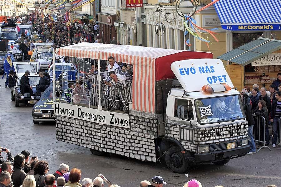 Rijeka, 190211.U sklopu Rijeckog Karnevala, danas je u prijepodnevnim satima po Korzu prosla povorka jubilarnog 20. Maskaranog auto rallya Pariz - Bakar u kojem sudjeluje oko 80-ak vozila i preko 200 maskara. Ovaj neozbiljni i veseli rally nastao je kao parodija na svjetski poznati rally Pariz-Dakar, sada znan kao Rally Dakar. Rijecki rally zapocinje u cetvrti Krimeja tzv. rijeckom Parizu, a zavrsava u gradicu Bakru, nedaleko od Rijeke. Duzina ovoga rally-a je 21,3 km, a vrijeme voznje 120 minuta sa prosjenom brzinom od 10,65 km na sat.Na slici: ove godine vise nego ikad maskare su ponajvise pronasle inspiraciju u vladi RH i HDZ-u. Maska koja je izazvala najvise simpatija je bio Apartman Remetinec - pokretni zatvor iz kojeg su gledatelje pozdravljala dobro nam poznata lica.Foto: Davor Zunic / CROPIX