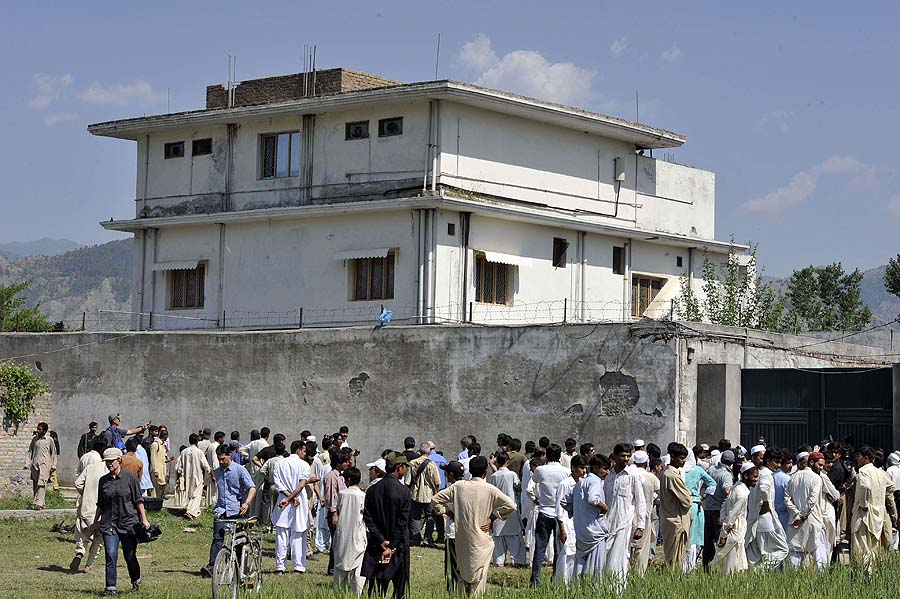 Pakistani media personnel and local residents gather outside the hideout of Al-Qaeda leader Osama bin Laden following his death by US Special Forces in a ground operation in Abbottabad on May 3, 2011. The bullet-riddled Pakistani villa that hid Osama bin Laden from the world was put under police control, as media sought to glimpse the debris left by the US raid that killed him. Bin Laden's hideout had been kept under tight army control after the dramatic raid by US special forces late May 1, 2011 in the affluent suburbs of Abbottabad, a garrison city 50 kilometres (30 miles) north of Islamabad.  AFP PHOTO/ AAMIR QURESHI