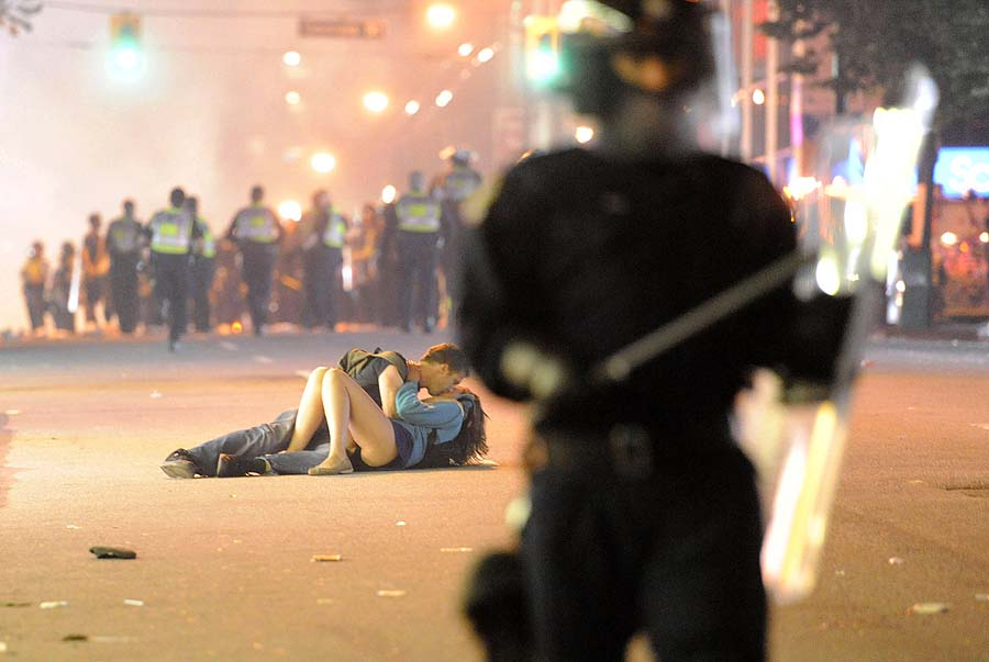 Riot police walk on the street amid rioting as a couple kiss on June 15, 2011 in Vancouver, Canada. Vancouver broke out in riots after their hockey team the Vancouver Canucks lost in Game Seven of the Stanley Cup Finals.  Rioters torched cars and smashed buildings in downtown Vancouver after the Boston Bruins won the Stanley Cup 4-0 over the Vancouver Canucks.     Rich Lam/Getty Images/AFP    == FOR NEWSPAPERS, INTERNET, TELCOS & TELEVISION USE ONLY ==