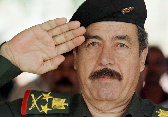 """(FILES)--Iraqi President Saddam Hussein's cousin and member of the Revolutionary Council Ali Hassan al-Majid salutes before unveiling a new statue of the president in Baghdad 02 May 1999. Ali Hassan al-Majid, better known as Saddam Hussein's enforcer """"Chemical Ali"""" was on January 17, 2010, sentenced to death for ordering the gassing of Kurds in the Iraqi village of Halabja, state television said.  AFP PHOTO / KARIM SAHIB"""