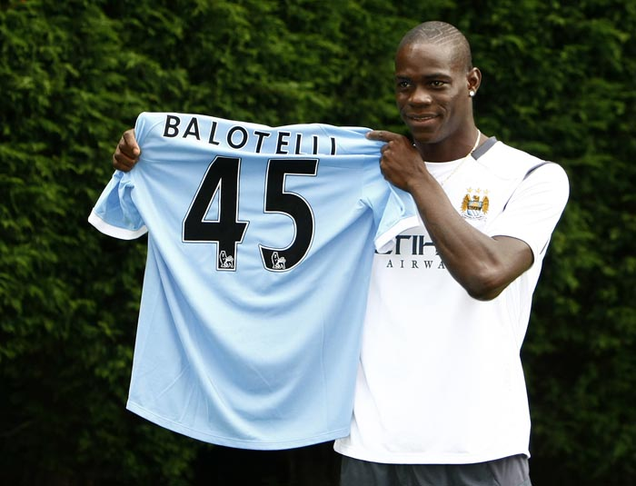 ** CORRECTS LOCATION TO CARRINGTON TRAINING GROUND **Manchester City's new signing Mario Balotelli holds up his shirt after a press conference held at the Carrington training ground, Manchester, England, Tuesday Aug. 17, 2010. Balotelli was signed from Inter Milan. (AP Photo/Tim Hales)