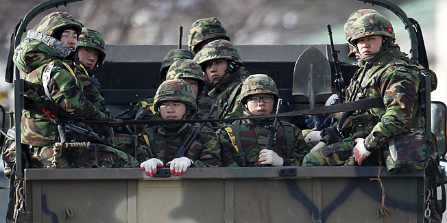 South Korean marines ride on the back of a truck on Yeonpyeong Island, South Korea, Monday, Dec. 6, 2010. South Korea is conducting naval firing drills just a day after North Korea warned such exercises would aggravate already high tensions between the rivals. (AP Photo/Yonhap, Kim hyun-tae)  KOREA OUT