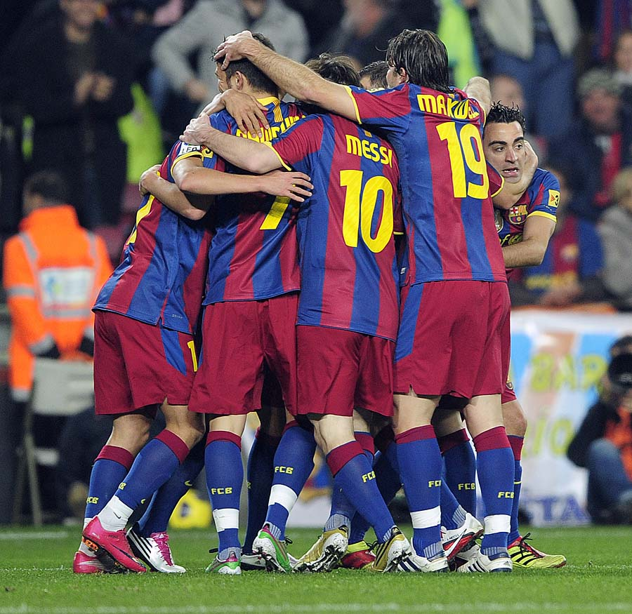 Barcelona's forward David Villa (C) is hugged by his teamates after scoring during the Spanish league football match FC Barcelona vs Real Sociedad on December 12, 2010 at Camp Nou stadium in Barcelona.     AFP PHOTO/ JOSEP LAGO