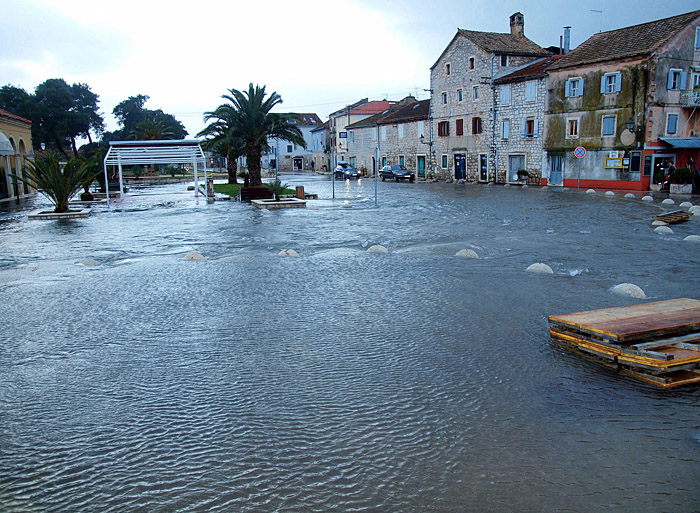 Stari Grad, 200210.Plimni val je napravio potop Starog Grada .Veliki plimni val koji je u petak poslijepodne podigao more i poplavio pola Starog Grada nanio je velike stete gradjanima, ali i vlasnicima poslovnih prostora u kojima rade kafici, trgovine i slicno. Starograjani tvrde da je bilo nekoliko plimnih valova, a vec na samom pocetku se izlilo cak 55 cm mora, tako da je pri povlacenju za sobom vuklo automobile, kontejnere, kante za smece i sve sto se naslo na rivi. Na slici je Stari Grad pod morem .Foto: Petar Botteri / CROPIX