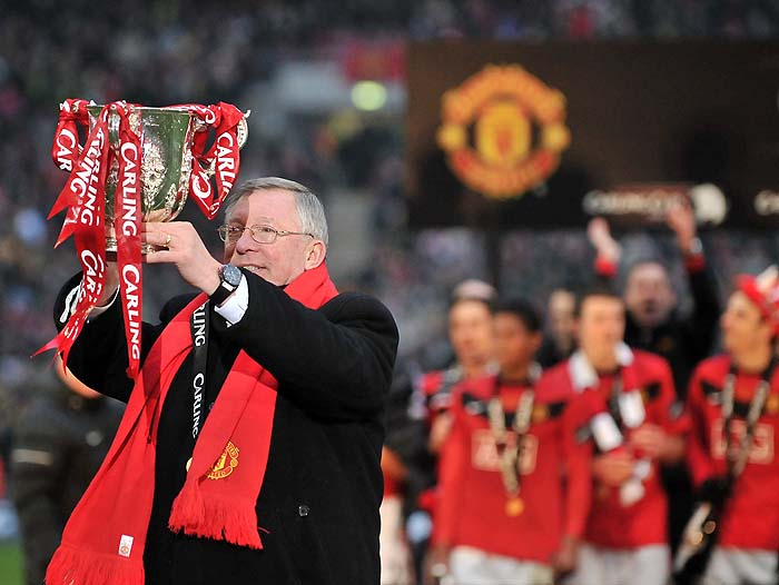Manchester United manager Sir Alex Ferguson celebrates with the trophy after his team beat Aston Villa 2-1 to win the 2010 Carling Cup Final at Wembley, in north London, on February 28, 2010. AFP PHOTO/CARL DE SOUZA