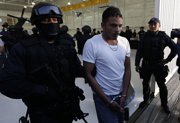 "Federal police escort handcuffed suspect Jose Roberto de la Sancha as he his presented to the press in Mexico City, Thursday, Oct. 22, 2009.  De la Sancha, detained along with five others in a recent police operation, is an alleged member of the Mexican drug cartel ""La Familia Michoacana,"" according to police.  (AP Photo/Gregory Bull)"