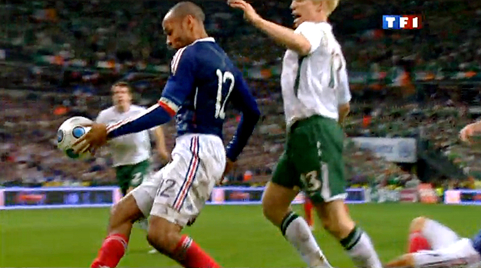 TV grab shows French forward Thierry Henry (L) eyes the ball next to Irish Paul Mc Shane during the World Cup 2010 qualifying football match France vs. Republic of Ireland on November 18, 2009 at the Stade de France in Saint-Denis, northern Paris. Superstar Thierry Henry was at the centre of a sensational cheating storm as France reached the World Cup finals along with Portugal, Greece and Slovenia.  France, the 1998 champions and 2006 runners-up, drew 1-1 with Ireland at the Stade de France in the second leg of their play-off for a 2-1 aggregate win. But the extra-time triumph came in controversial circumstances when French skipper Henry appeared to control the ball with his hand before his angled pass allowed William Gallas to head in the crucial 103rd-minute goal.       AFP PHOTO GRAB / TF1 /