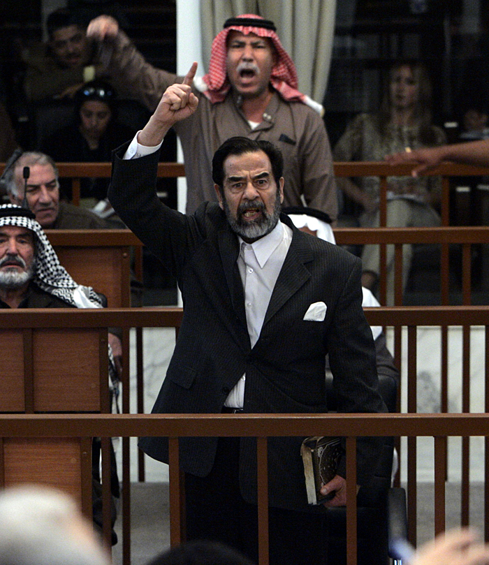 ** FOR USE AS DESIRED, PHOTOS OF THE DECADE ** FILE - Former Iraqi President Saddam Hussein, front center, and Barzan Ibrahim al-Tikriti, back center, berate the court during their trial in Baghdad, in this Dec. 5, 2005, file photo.    (AP Photo/David Furst, Poo, File)
