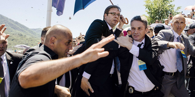 Bodyguards try to protect Serbian Prime Minister Aleksandar Vucic (C) from stones hurled at him by an angry crowd at the Potocari Memorial Center, near the eastern Bosnian town of Srebrenica on July 11, 2015. Tens of thousands of people gathered in Srebrenica on July 11 to commemorate the 20th anniversary of the massacre of thousands of Muslims in the worst mass killing in Europe since World War II. Serbian Prime Minister Aleksandar Vucic was forced to leave the Srebrenica memorial when the crowd started to chant 'Allahu Akbar' (God is Great) and to throw stones. AFP PHOTO / DIMITAR DILKOFF