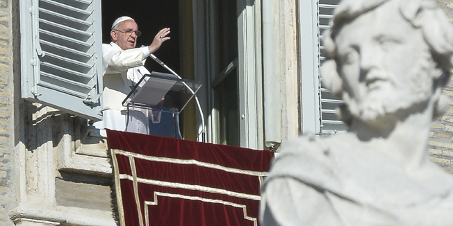 Pope Francis greets the crowd from the window of the Apostolic Palace overlooking St.Peter's square during his Angelus prayer on January 1, 2015 at the Vatican. AFP PHOTO / ANDREAS SOLARO