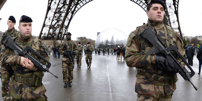 """French soldiers patrol in front of the Eiffel Tower on January 8, 2015 in Paris. France announced an unprecedented deployment of thousands of troops and police to bolster security at """"sensitive"""" sites including Jewish schools Monday, the day after marches that drew nearly four million people across the country in tribute to the 17 victims of a three-day killing spree in Paris. The killings began on January 7 with an assault on the Charlie Hebdo satirical magazine in Paris that saw two brothers massacre 12 people including some of the country's best-known cartoonists and the storming of a Kosher supermarket on the eastern fringes of the capital which killed 4 local residents. AFP PHOTO / BERTRAND GUAY AFP/AFP/BERTRAND GUAY/STF /tsc"""