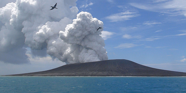 TOPSHOTSThis view taken on January 17, 2015 from a boat at sea shows frigate birds flying on the thermals from the new vent as steam and gas rise from the eruption of a volcano, some 65 kilometres (40 miles) northwest of the South Pacific nation Tonga's capital Nuku'alofa. The Tongan volcano has created a substantial new island since it began erupting in December, spewing out huge volumes of rock and dense ash that has killed nearby vegetation, officials said on January 16.  The Lands and Natural Resources Ministry said the volcano was erupting from two vents, one on the uninhabited island of Hunga Ha'apai and the other underwater about 100 metres offshore.        AFP PHOTO / Matangi Tonga / Mary Lyn Fonua