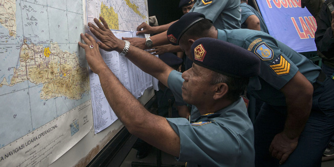 Indonesian Air Force officials show maps to journalists of the search area for the missing Malaysian air carrier AirAsia flight QZ8501, at the airport in Surabaya, East Java, on December 29, 2014. The AirAsia plane which went missing with 162 people on board en route for Singapore is likely at the bottom of the sea, Indonesia's National Search and Rescue Agency chief said on December 29. AFP PHOTO / Juni KRISWANTO