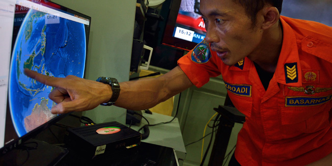 TOPSHOTSAn official from Indonesia's national search and rescue agency in Medan, North Sumatra points at his computer screen to the position where AirAsia flight QZ8501 went missing off the waters of Indonesia on December 28, 2014. The AirAsia Airbus plane with 162 people on board went missing en route from Indonesia to Singapore early on December 28, officials and the airline said, in the third major incident to affect a Malaysian carrier this year. AFP PHOTO / Sutanta ADITYA