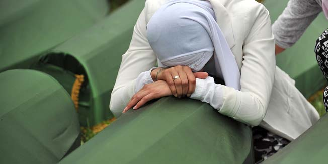 A Bosnian Muslim woman, survivor of the Srebrenica 1995 massacre cries by the coffin of a relative, layed out among others at the memorial cemetery in the village of Potocari near the eastern-Bosnian town of Srebrenica, on July 11, 2014. Several thousand people gathered on July 11 in Srebrenica for the 19th anniversary of the massacre of some 8,000 Muslim males by ethnic Serbs forces, Europe's worst atrocity since World War II. A total of 175 newly-identified massacre victims will be laid to rest after a commemoration ceremony held in Potocari, just outside the ill-fated Bosnian town. AFP PHOTO / ELVIS BARUKCIC