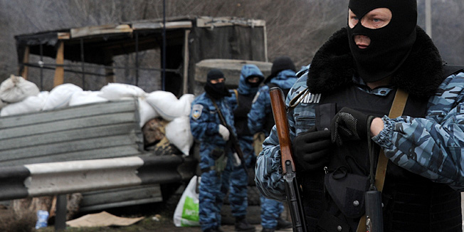 Armed masked men who call  themselves members of Ukraine's disbanded elite Berkut riot police force stand at their checkpoint under a Russian flag on a highway that connect Black Sea Crimea  peninsula to mainland Ukraine near the city of Armyansk, on February 28, 2014. The spiralling tensions in a nation torn between the West and Russia took today a severe new turn when Ukraine's interim president Oleksandr Turchynov accused Russian soldiers and local pro-Kremlin militia of staging raids on Crimea's main airport and another base on the southwest of the peninsula where pro-Moscow sentiments run high. AFP PHOTO / VIKTOR DRACHEV