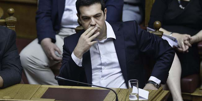 Greek Prime Minister Alexis Tsipras looks on during a parliamentary session in Athens on June 27, 2015. Greece will hold a referendum on July 5 on the outcome of negotiations with its international creditors taking place in Brussels on June 27, Prime Minister Alexis Tsipras announced. AFP PHOTO / ANGELOS TZORTZINIS