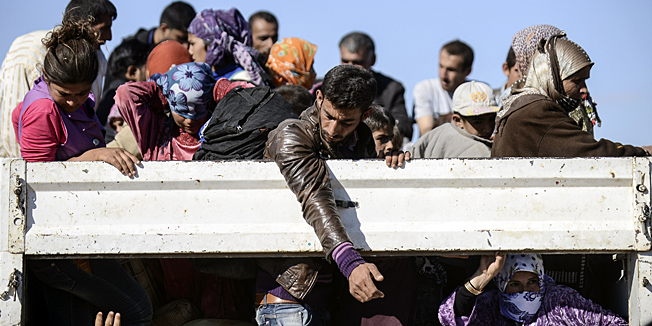 Syrian Kurdish people get into bus after crossing the border between Syria and Turkey after several mortars hit both side in the southeastern town of Suruc, in the Sanliurfa province, on September 30, 2014. Tens of thousands of Syrian Kurds flooded into Turkey fleeing an onslaught by the Islamic State (IS) group that prompted an appeal for international intervention. Some refugees now want to return to protect their homes and join the fight against Islamic State group militants. AFP PHOTO / BULENT KILIC