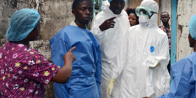 Health workers in protective gear pose at the entrance of the Ebola treatment unit of the John F. Kennedy Medical Center, in the Liberian capital Monrovia, on October 13, 2014. Health workers across Liberia went on strike on Monday to demand danger money to care for the sick at the heart of a raging Ebola epidemic that has already killed dozens of their colleagues. Doctors, nurses and carers in west Africa are on the frontline of the worst-ever outbreak of Ebola, which has killed more than 4,000 people, mostly in Guinea, Sierra Leone and the hardest-hit, Liberia. AFP PHOTO / ZOOM DOSSO