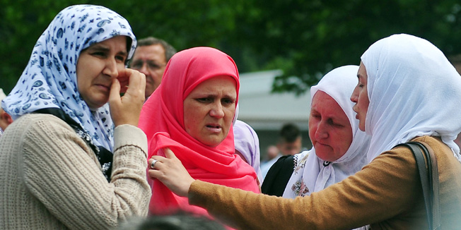 Bosnian Muslim woman, Hava Muhic (2nd L), survivor of Srebrenica 1995 massacre, observes burial of the body of her child, the youngest victim, during a mass burial at a memorial cemetery in the village of Potocari near the eastern Bosnian town of Srebrenica on July 11, 2013. Bosnia buried 409 victims of the Srebrenica massacre on July 11, including a newborn baby, on the 18th anniversary of the worst slaughter in post-war Europe. More than 15,000 people travelled to Potocari, near Srebrenica to attend the mass funeral of victims whose remains were found in mass graves and only identified almost two decades after the 1995 killing.  AFP PHOTO / ELVIS BARUKCIC