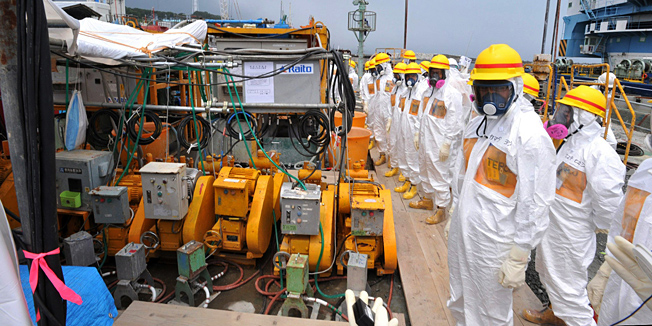 This photo taken on August 6, 2013 shows local government officials and nuclear experts inspecting a facility to prevent seeping of contamination water into the sea at Tokyo Electric Power's (TEPCO) Fukushima Dai-ichi nuclear plant in Okuma, Fukushima prefecture. Japan will accelerate efforts to prevent more radioactive groundwater from seeping into the ocean at the crippled Fukushima nuclear plant, government officials said on August 7, as critics slam its operator's handling of the issue.  JAPAN OUT      AFP PHOTO / JAPAN POOL via JIJI PRESS