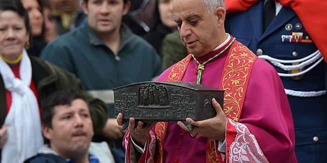 Italian archbishop Rino Fisichella holds the ashes of St Peter before a ceremony of Solemnity of Our Lord Jesus Christ the King at St Peter's square on November 24, 2013 at the Vatican.  AFP PHOTO / VINCENZO PINTO