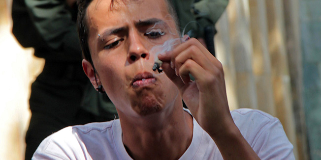 "A man smokes marijuana during a demo for its legalization in Medellin, Colombia on May 7, 2011. Hundreds of youngsters marched in several events throughout Latin America, under the slogan ""Cultivate your rights"".  AFP PHOTO/ FREDY AMARILES"