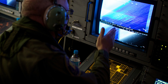 A crewman on board an RAAF AP-3C Orion aircraft looka at his radar screens whilst searching for the missing Malaysia Airways Flight MH370 over the Indian Ocean on March 24, 2014. Australian Prime Minister Tony Abbott told Parliament on March 24 that a Royal Australian Air Force P-3 Orion aircraft had located two new objects floating in the southern Indian Ocean.  AFP PHOTO/POOL/RICHARD WAINWRIGHT