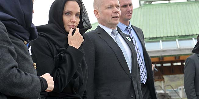 Hollywood actress Angelina Jolie (L) and British Foreign Minister William Hague (R) pay their respects at Srebrenica-Potocari Genocide Memorial cemetery, near Srebrenica, on March 28, 2014. Jolie and Hague are in Sarajevo for a conference on sexual violence in war organised by Bosnia's defence ministry.  Around 20,000 women, mostly Muslim, were raped during Bosnia's inter-ethnic war in the 1990s, according to local estimates. AFP PHOTO / ELVIS BARUKCIC